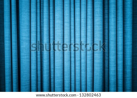 Close-up view of bright blue curtain in thin and thick vertical folds made of dense fabric. Textured abstract backgrounds and wallpapers. Materials and textiles. - stock photo