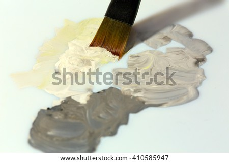 Close up View of Brush mixing grey yellow beige colors Paints on white Palette - stock photo