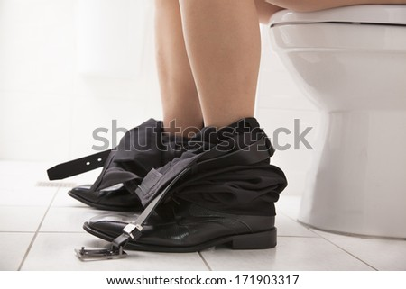 Close-up view of  business male sitting on the toilet seat - stock photo