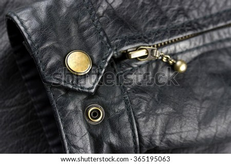 Close-up view of button on the sleeve of leather jacket - stock photo
