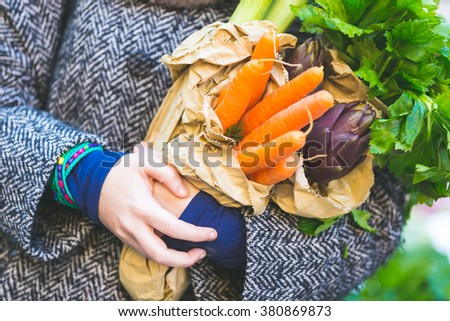 Close up view of carrots and some other vegetables held by a woman at market. They are fresh and natural, she is carrying them on some recycled paper bags, with strong concept of sustainability. - stock photo