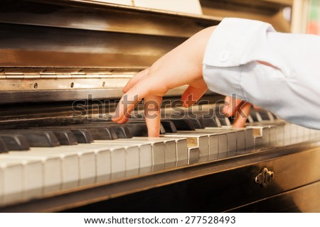 Close-up view of child's hands playing on piano - stock photo
