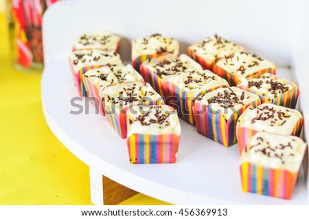 Close up view of colorful square cupcake with chocolate rice on top. Selective focus and shallow DOF. - stock photo