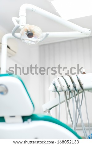 Close-up view of dental tools and professional chair at dentist - stock photo