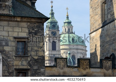 Close-up view of dome and belltower of Saint Nicholas Cathedral between towers of Charles Bridge on the side of Lesser Town in Prague, Czech Republic. - stock photo