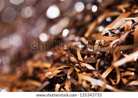 Close-up view of entangled magnetic tapes in various hues of brown, taken off (many) audio cassettes. Shallow depth of field, focus on foreground. - stock photo