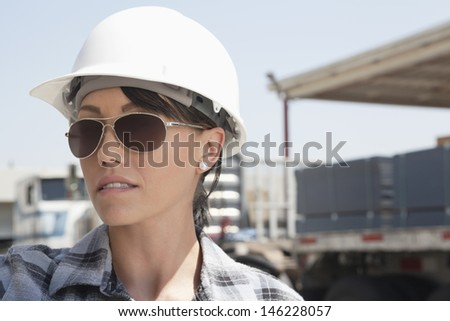 Close-up view of female industrial worker wearing hardhat and sunglasses - stock photo