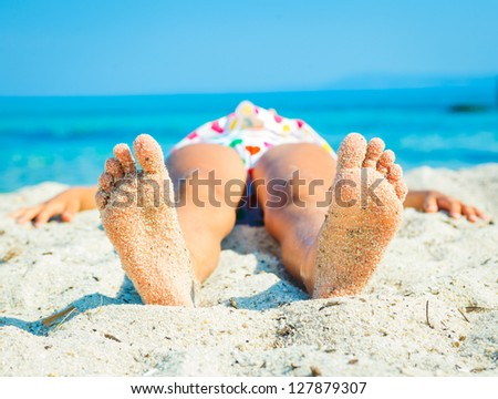 Close-up view of foots by the girl lying on the sand beach. - stock photo