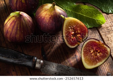 close up view of fresh figs and knife on color back - stock photo