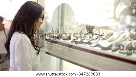 Close up view of girl looking at jewelry in window case at jeweler's shop - stock photo