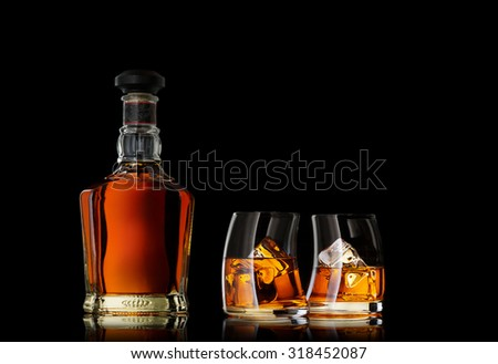 close up view of glasses with ice and whiskey and a bottle aside - stock photo