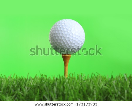 Close up view of golf ball on tee on green background - stock photo