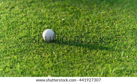 Close-up view of golf ball on the green grass. Golf ball on fairway of beautiful golf course at summer sunset. Success, competition and leisure, lifestyle concept. Panorama style with copyspace. - stock photo