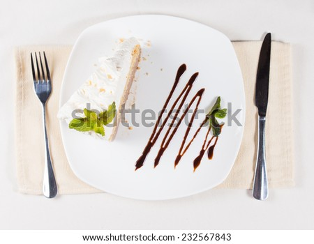 Close up View of Gourmet Slice of Sweet Cake with Green Leaves on Top of Whipped Cream, Prepared on White Plate and Served on the Table with Utensils on Sides. - stock photo