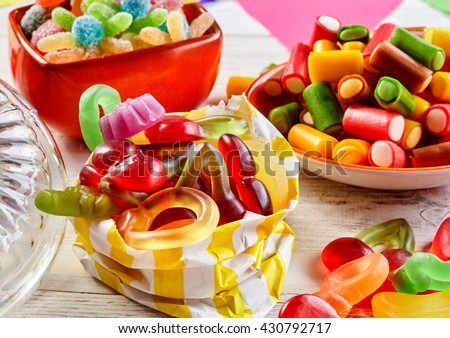 Close up view of gummy worms in stripped bag besides bowls of delicious sweets set on a rustic wood table - stock photo