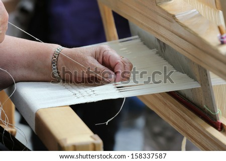Close-up view of hand loom weaver's hands at work - stock photo