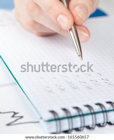 Close up view of hand writing in the notebook lying on the diagrams - stock photo