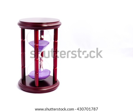 Close-up view of hourglass/sandglass/sand timer with sand falling isolated on white background. Sand flowing inside hour glass. Time constraints, limitations and deadline concept with copyspace. - stock photo