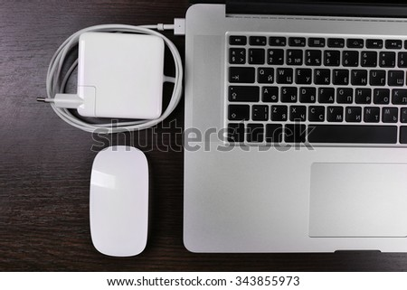 Close-up view of laptop and equipment at working place on black wooden background - stock photo