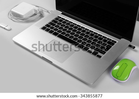 Close-up view of laptop and equipment at working place on silver glossy background - stock photo