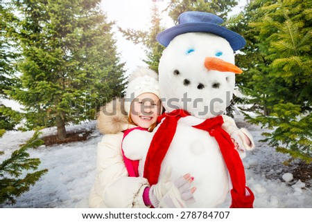 Close-up view of laughing girl and snowman - stock photo