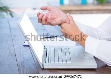 Close up view of man massaging his wrist over a laptop - stock photo