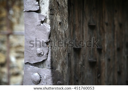 close up view of medieval castle gate door, weathered wood and metal armor plate - stock photo
