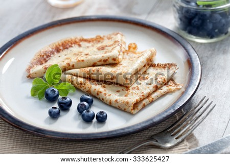 close up view of nice yummy crepes with blueberry on table - stock photo