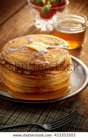 close up view of nice yummy pancakes with honey on table - stock photo
