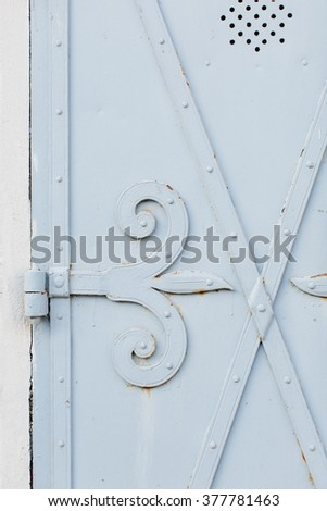 Close up view of old painted white gate hinge with bits of rust showing through surface and speaker holes at top - stock photo