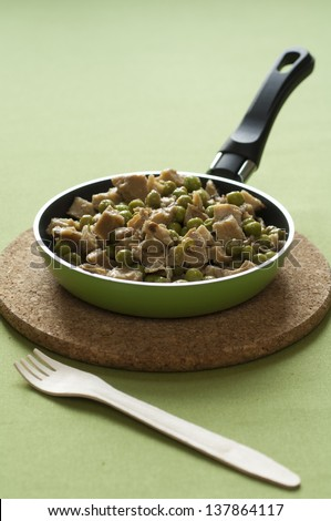 Close-up view of organic Seitan chops with green peas in a hot pan placed on a cork dish with a wooden fork - stock photo