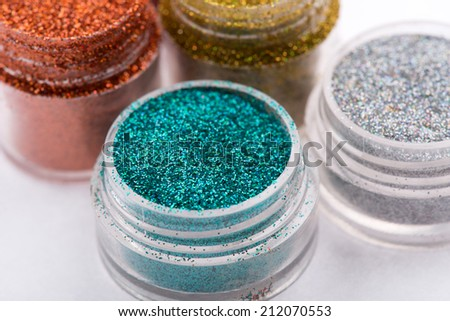 Close-up view of  powder eye shadows  in red, blue,  yellow and silver colours isolated on white background with selective focus on blue powder eyeshadow - stock photo