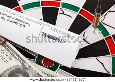 Close up view of red arrow and one hundred dollar bill and US tax form on dart board. - stock photo