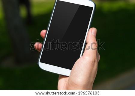 Close up view of smart phone with blank black screen on blurry natural background. - stock photo
