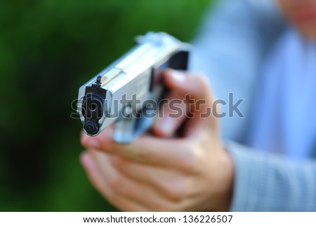 Close up view of someone pointing a gun at the camera - stock photo