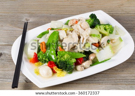 Close up view of stir fried white chicken pieces with broccoli, snow peas, peppers and mushroom in white plate on rustic wood setting.  - stock photo