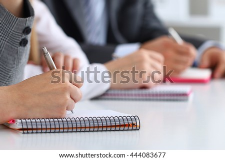 Close up view of students or businesspeople hands writing something during conference. Business meeting, blogging or professional education concept - stock photo