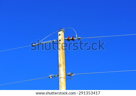 Close-up view of telephone pole and wire with vibrant blue sky background, shallow DOF - stock photo