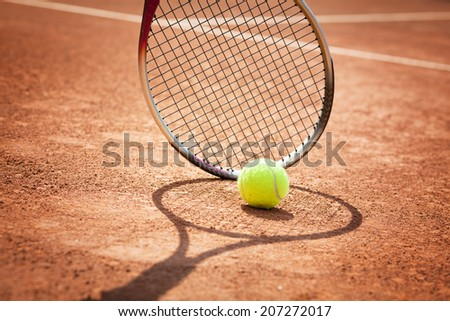 Close up view of tennis racket and ball on the clay tennis court - stock photo