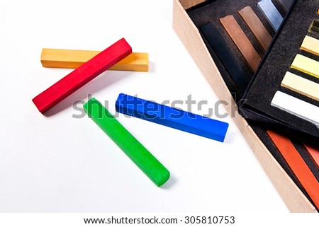 Close up view of the box with colorful chalk pastels on the white background. - stock photo