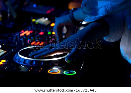 Close up view of the colourful controls on the deck at night with the hands of a DJ mixing and scratching music at a concert using vinyl records on a turntable - stock photo