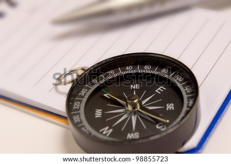 Close up view of the Compass on the white note-book as background - stock photo