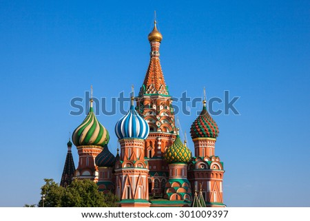 Close-up view of the famous Saint Basil's Cathedral with moon rising between its domes, Red Square, Moscow, Russia. - stock photo
