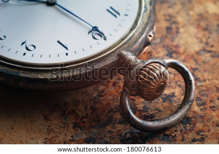 Close up view of the gears and mainspring in the mechanism of a silver pocket watch on old paper  - stock photo