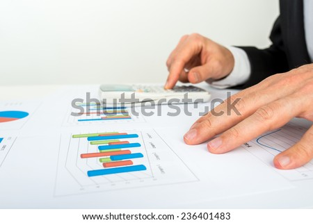 Close up view of the hands of a businessman analyzing a bar graph using a manual calculator to check the statistics and projections. - stock photo