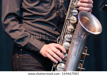 Close up view of the hands of a male saxophonist playing a tenor saxophone in an orchestra, a reed woodwind instrument popular in jazz, classical and blues music - stock photo