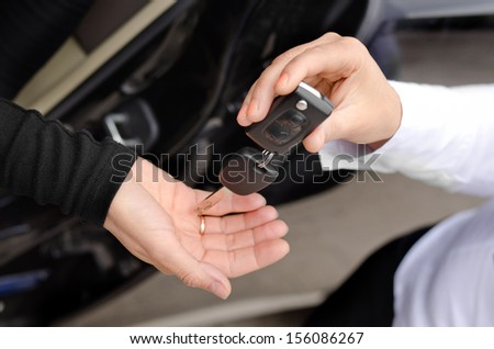 Close up view of the hands of a woman handing over a set of car keys to a second woman holding out her hand, conceptual image - stock photo