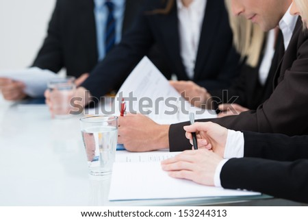 Close up view of the hands of business people taking notes in a meeting seated at a table - stock photo