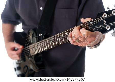 Close-up view of the left hand of a man fingering a chord on the fingerboard of an electric guitar. - stock photo