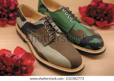Close-up view of the pair stylish and elegant men's shoes with camo print and red flowers around on wooden table on light background - stock photo